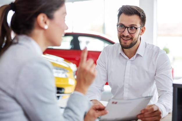Glimlachende klant zit aan tafel met autoverkoper, houdt aanbieding vast en luistert naar autoverkoper over gemakken