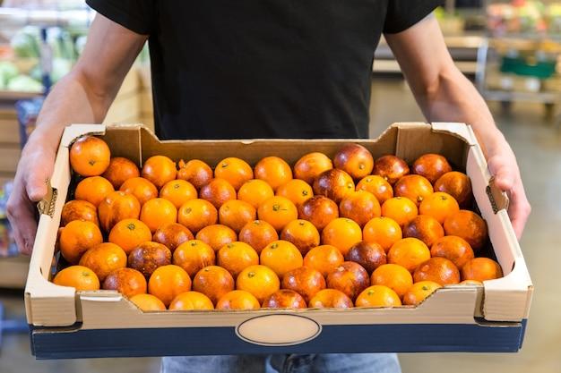 Glimlachende klanten die siciliaanse sinaasappelen in kruidenierswinkelsectie kopen