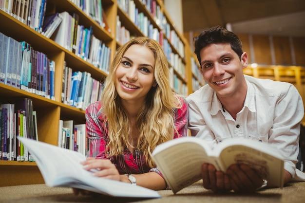 Glimlachende klasgenoten die boek lezen terwijl het leunen op boekenrek in bibliotheek