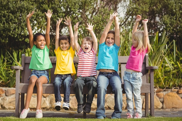 Glimlachende klasgenoten die op bank en het toejuichen zitten