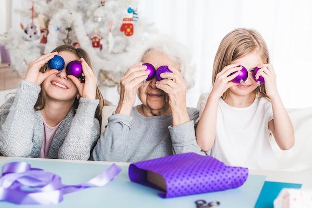 Glimlachende kleindochters spelen met decoratieve ballen zoals ogen met oma met kerstmis