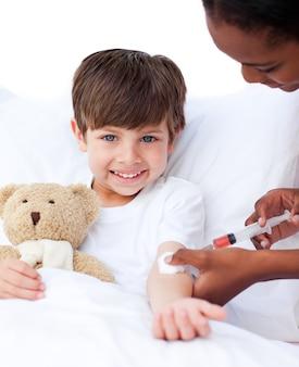 Glimlachende kleine jongen die een injectie ontvangt