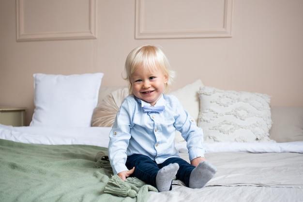 Glimlachende kleine jongen die op bed ligt. mensen, kinderen, rust en comfortconcept.