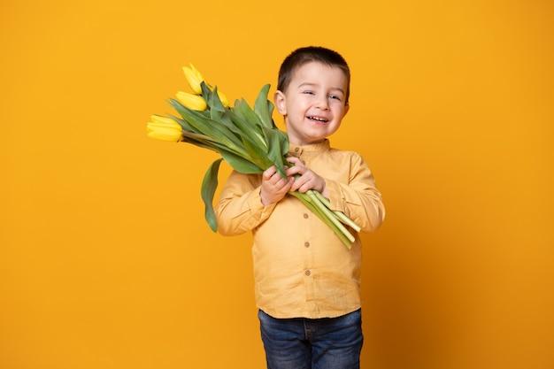 Glimlachende kleine jongen op gele studioachtergrond. vrolijk gelukkig kind met tulpen bloemboeket.