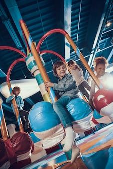 Glimlachende kleine kinderen die van het berijden van carrousel genieten