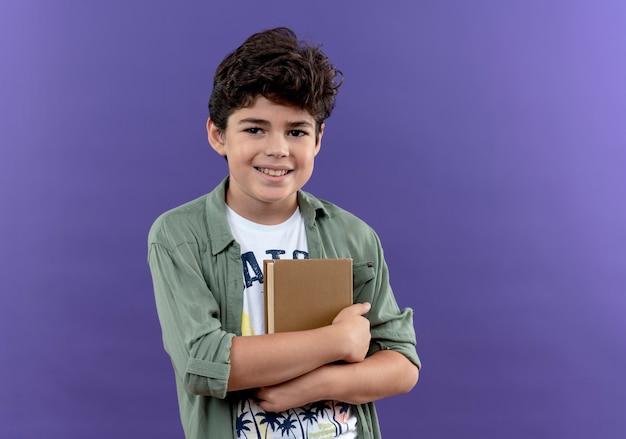 Glimlachende kleine schooljongen omhelsde boeken die op purpere muur worden geïsoleerd