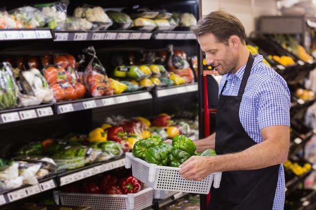 Glimlachende knappe arbeider die een doos met groente houdt