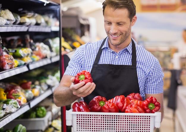 Glimlachende knappe arbeider die een groente op haar hand neemt