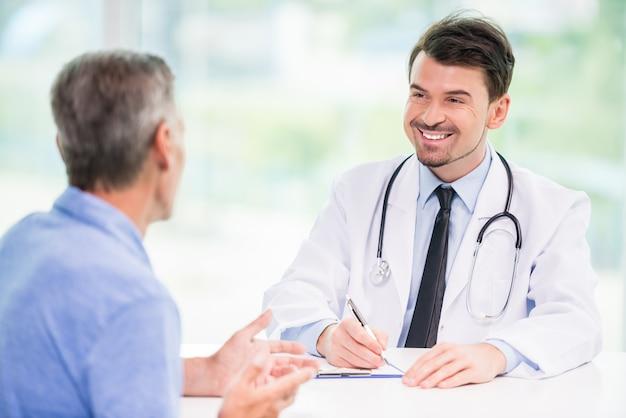 Glimlachende knappe arts die met patiënt op zijn kantoor spreken.