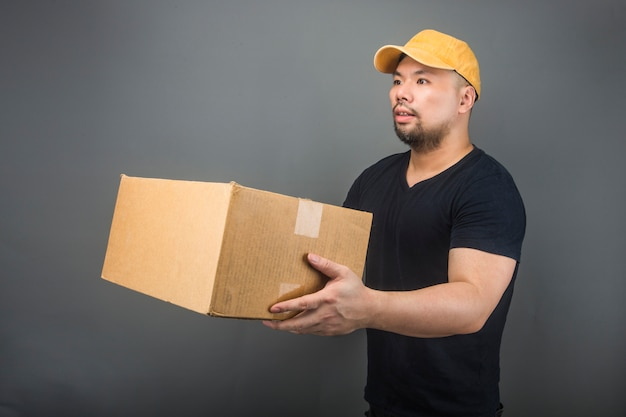 Glimlachende knappe aziatische leveringsmens die glb, het geven en het dragen van pakket, kartondoos, bewegende huisdag en uitdrukkelijke leveringsconcept dragen