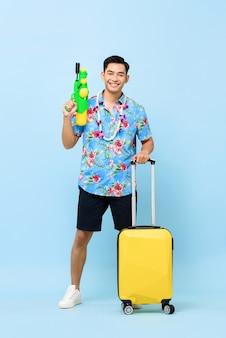 Glimlachende knappe aziatische toeristenmens die met waterkanon en bagage reizen tijdens songkran-festival