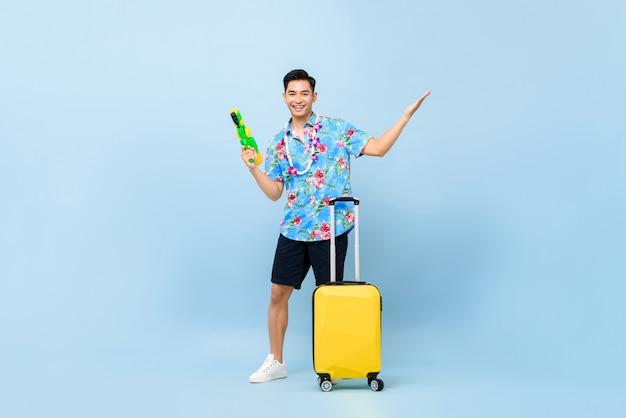 Glimlachende knappe aziatische toeristenmens die met waterkanon en bagage tijdens songkran reizen