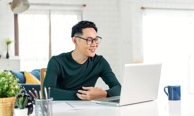 Glimlachende knappe aziatische zakenman die op afstand vanuit huis werkt. hij is webinar videoconferentie.