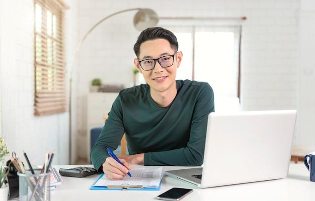 Glimlachende knappe aziatische zakenman die vanuit huis werkt.