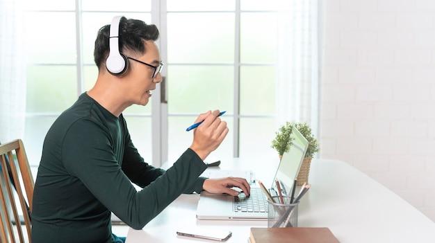 Glimlachende knappe aziatische zakenman draagt een koptelefoon die op afstand werkt vanuit huis. hij is een webinar-videoconferentie