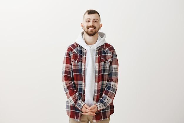Glimlachende knappe bebaarde hipster man kijkt naar voren, staande in bescheiden pose