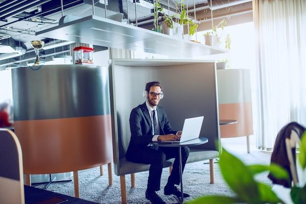 Glimlachende knappe blanke bebaarde zakenman in pak, met bril en koptelefoon zittend op de werkplek en typen op laptop tijdens het kijken naar camera.