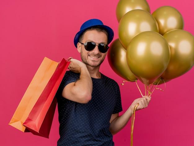 Glimlachende knappe blanke man in zonnebril met blauwe feestmuts houdt helium ballonnen en papieren boodschappentassen geïsoleerd op roze achtergrond met kopie ruimte