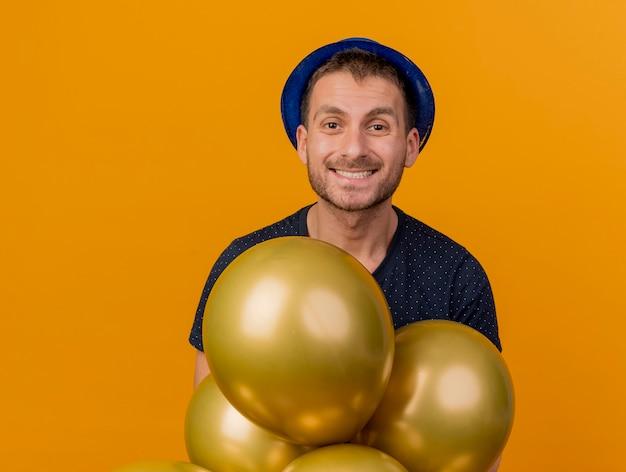 Glimlachende knappe blanke man met blauwe feestmuts houdt helium ballonnen geïsoleerd op een oranje achtergrond met kopie ruimte