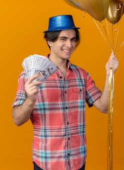 Glimlachende knappe blanke man met blauwe feestmuts houdt heliumballonnen en geld vast