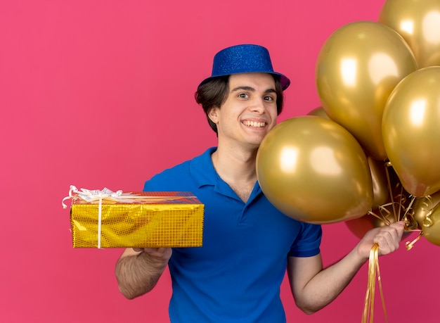 Glimlachende knappe blanke man met blauwe feestmuts houdt heliumballonnen en geschenkdoos vast