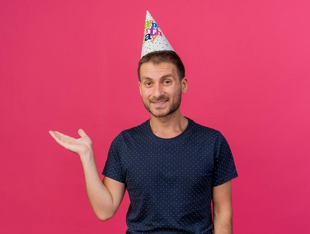 Glimlachende knappe blanke man met verjaardag glb houdt hand open geïsoleerd op roze achtergrond met kopie ruimte