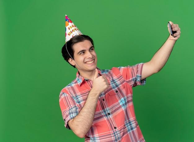 Glimlachende knappe blanke man met verjaardagspet duimen omhoog houdend en kijkend naar de telefoon