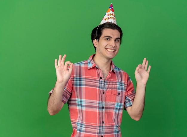 Glimlachende knappe blanke man met verjaardagspet-gebaren ok handteken met twee handen