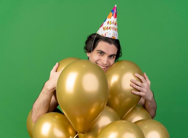 Glimlachende knappe blanke man met verjaardagspet houdt heliumballonnen vast