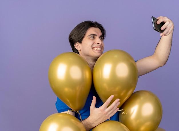 Glimlachende knappe blanke man staat met heliumballonnen vast te houden en te kijken naar de telefoon die selfie maakt