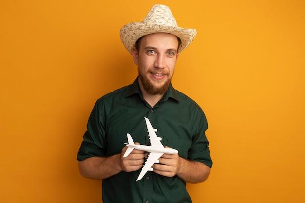 Glimlachende knappe blonde man die met strandhoed modelvliegtuig op sinaasappel houdt
