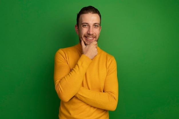 Glimlachende knappe blonde man houdt kin op groen