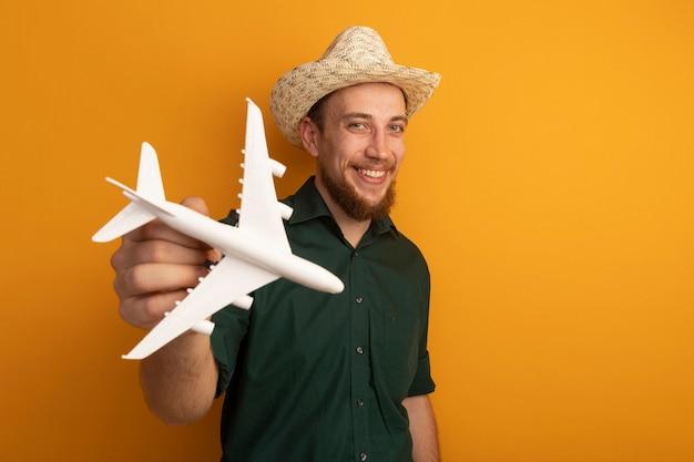 Glimlachende knappe blonde man met strandhoed houdt modelvliegtuig op oranje