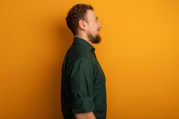 Glimlachende knappe blonde man staat zijwaarts op oranje