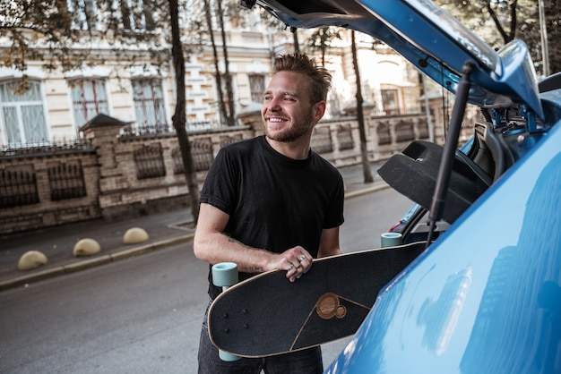 Glimlachende knappe blonde mannelijke skater die longboard op de kofferbak zet en iemand op de achtergrond van de stad ziet. extreme sporten. stedelijke hobby's. vrije tijd concept. vrije tijd, buitenshuis concept.