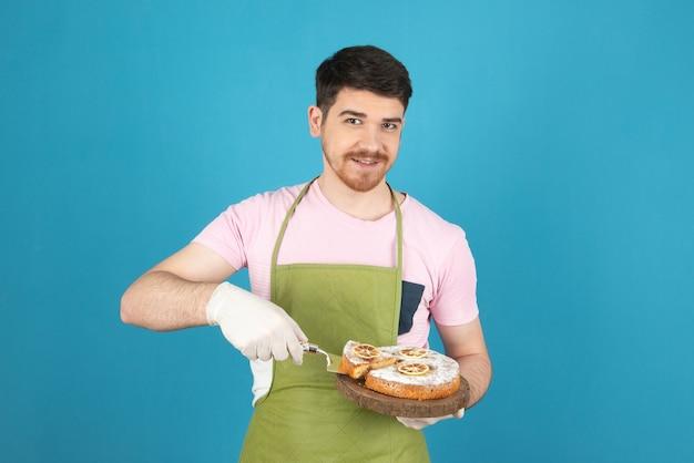 Glimlachende knappe chef-kok die verse cake serveert.