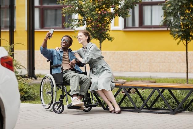 Glimlachende knappe jonge gehandicapte afro-amerikaanse man met een bril die in een rolstoel zit en een selfie neemt met zijn vriendin buitenshuis Premium Foto