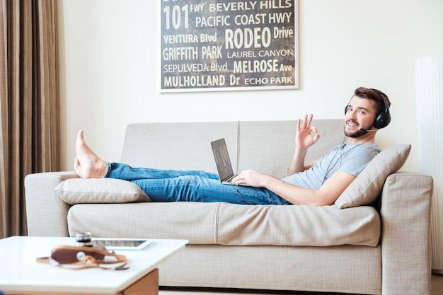 Glimlachende knappe jonge man met laptop in headset met videoconferentie thuis