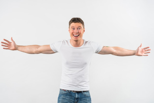 Glimlachende knappe jonge mens die haar wapens outstretching die op witte achtergrond wordt geïsoleerd
