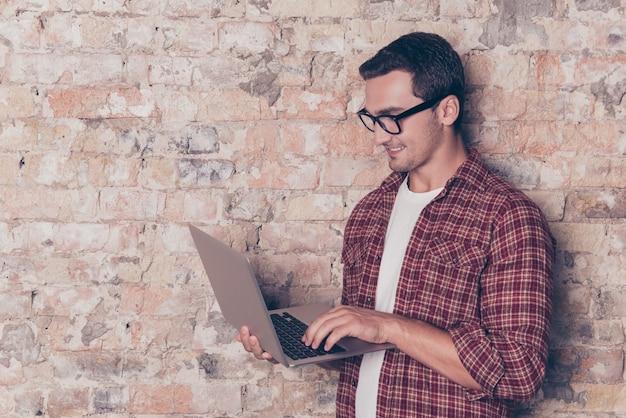 Glimlachende knappe jonge mens die in glazen zijn moderne laptop houdt