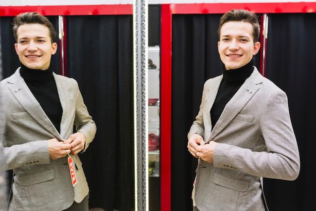 Glimlachende knappe jonge mens die jasje voor spiegel probeert