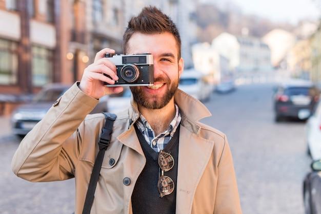 Glimlachende knappe jonge mens op stadsstraat die een beeld van uitstekende camera nemen