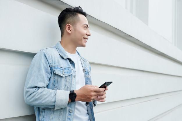 Glimlachende knappe jonge vietnamese man in spijkerjasje met smartphone tegen de bouwmuur
