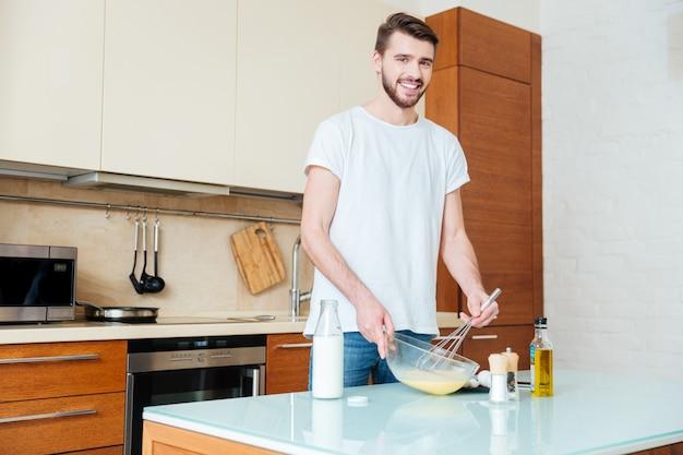 Glimlachende knappe jongeman die eieren in een kom zwaait en omelet in de keuken kookt