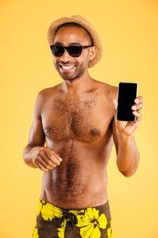 Glimlachende knappe jongeman die in hoed en zonnebril leeg schermsmartphone houdt over oranje muur
