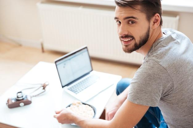Glimlachende knappe jongeman die laptop gebruikt en thuis ontbijtgranen met melk eet
