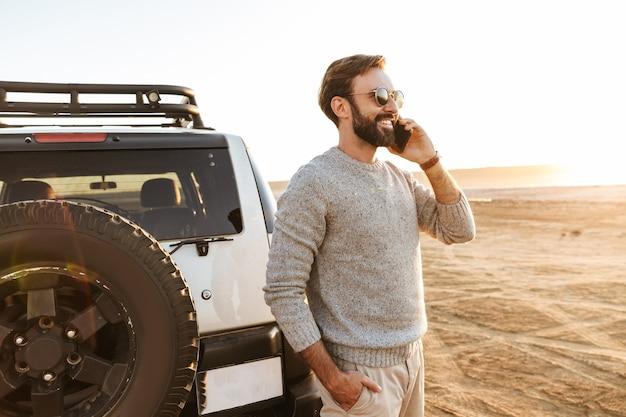 Glimlachende knappe jongeman die mobiele telefoon gebruikt terwijl hij bij de auto op het zonnige strand staat en belt