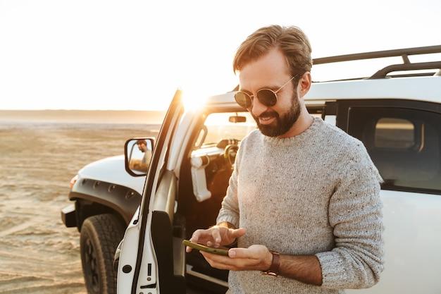 Glimlachende knappe jongeman die mobiele telefoon gebruikt terwijl hij bij de auto op het zonnige strand staat, sms't