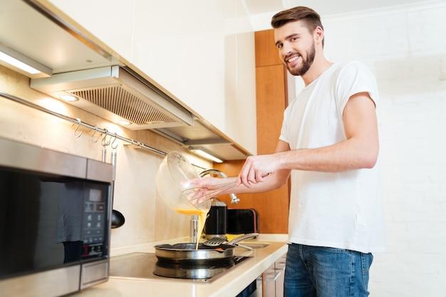 Glimlachende knappe jongeman die staat en omelet kookt voor het ontbijt