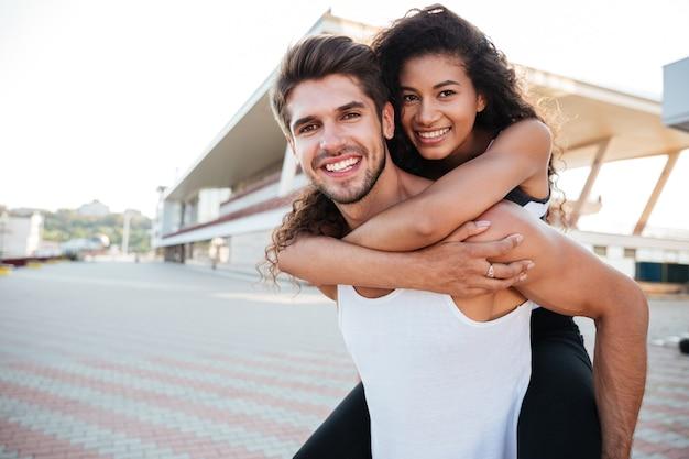 Glimlachende knappe jongeman die zijn vriendin in de buitenlucht vasthoudt
